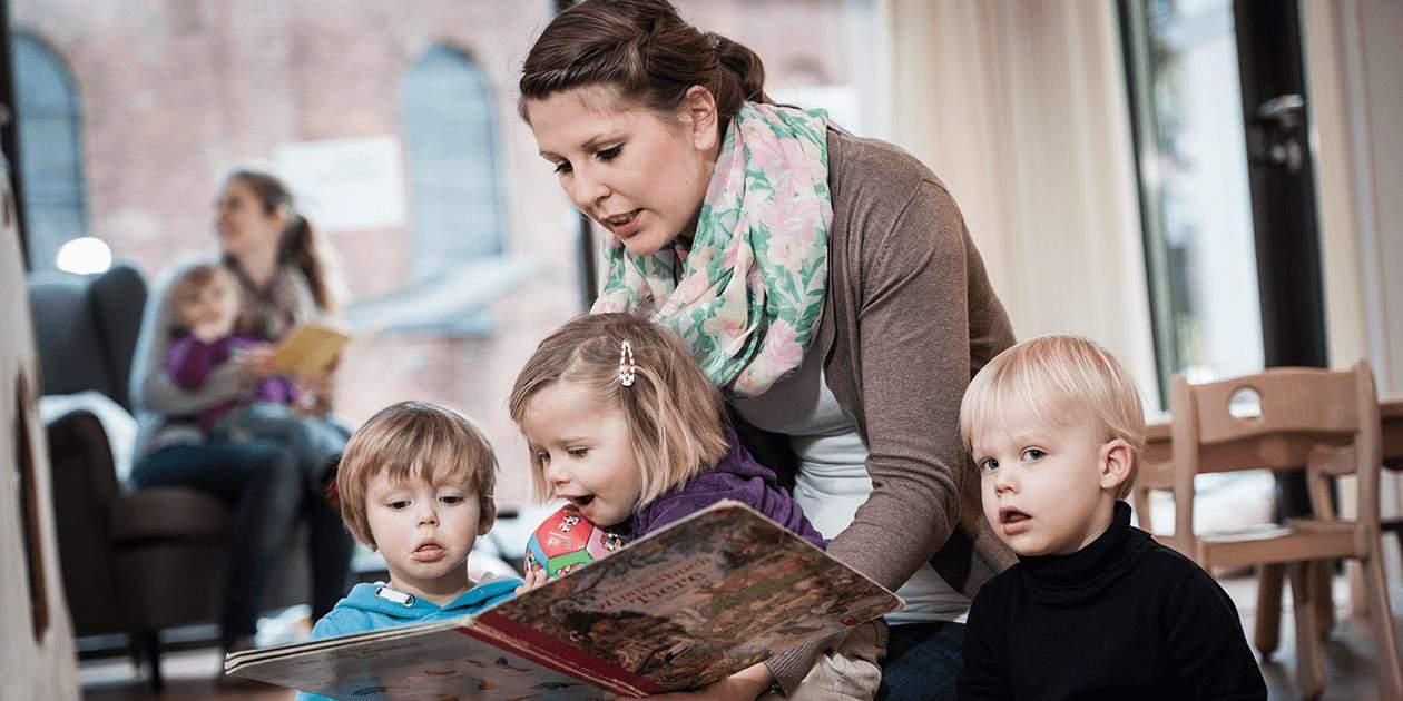 Eine Erzieherin der St. Marien Kita liest mit Kindern gemeinsam ein Buch.